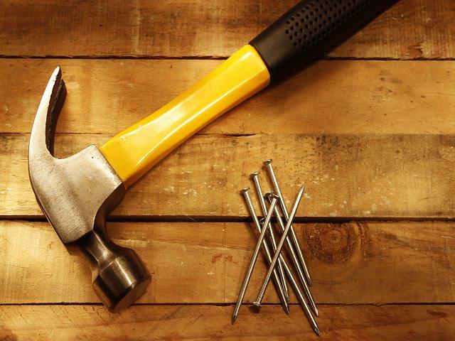 Молоток и гвозди на деревянной поверхности