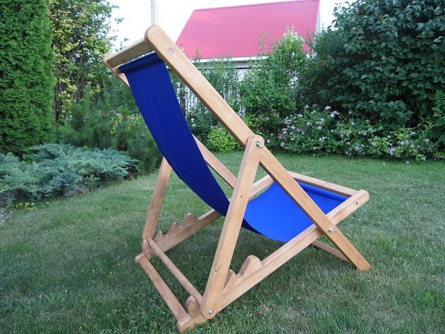 Шезлонг с синим сиденьем на газоне