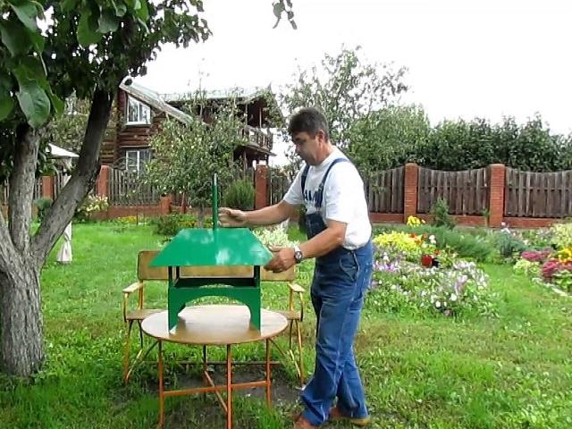 Мужчина делает козырек на трубу дымохода своими рукками