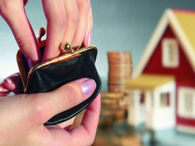 Кошелек с деньгами на фоне дома