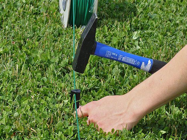 Вбивание колышка для создания автоматической газонокосилки
